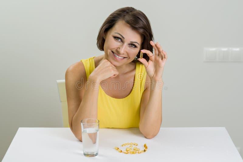 Femme de sourire prenant la pilule Omega-3 d'huile de poisson Vitamine D, E, un Fis photos libres de droits
