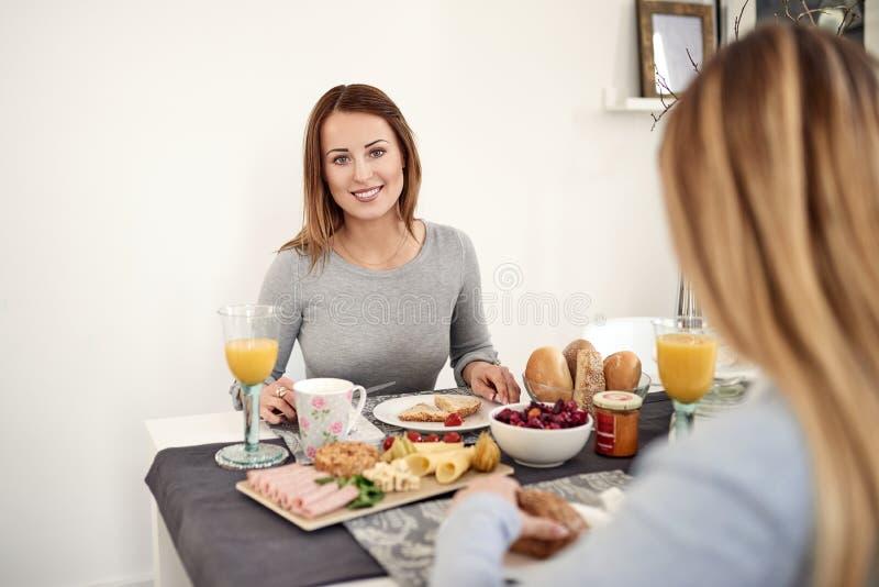 Femme de sourire prenant le petit déjeuner avec sa fille photos libres de droits