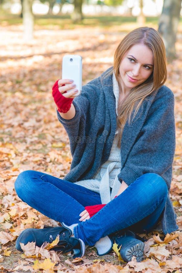Download Femme De Sourire Prenant Un Selfie En Parc D'automne Photo stock - Image du herbe, sourire: 45355506