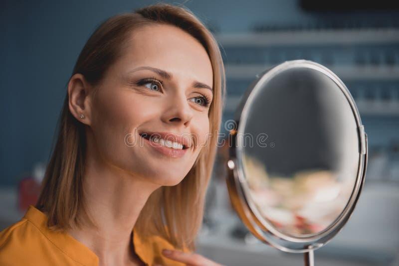 Femme de sourire regardant le miroir image libre de droits