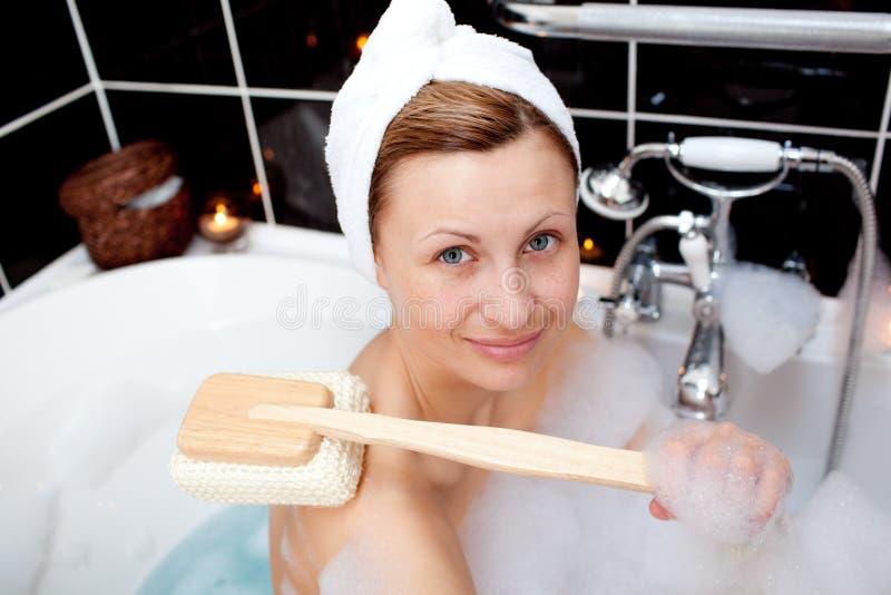 Femme de sourire rentrant un bain de bulle photo stock