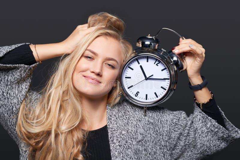 Femme de sourire s'étirant tenant le grand réveil images libres de droits