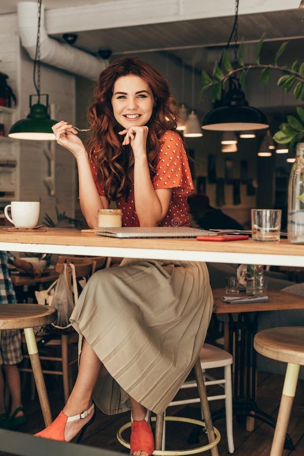 femme de sourire s'asseyant à la table avec le dessert et l'ordinateur portable images libres de droits