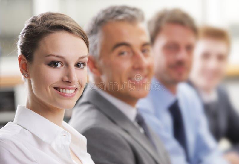 Femme de sourire s'asseyant lors d'une réunion d'affaires avec des collègues images stock
