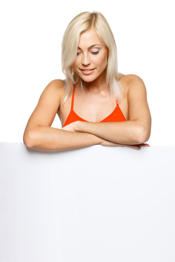 Femme de sourire se penchant sur un panneau-réclame blanc blanc images libres de droits