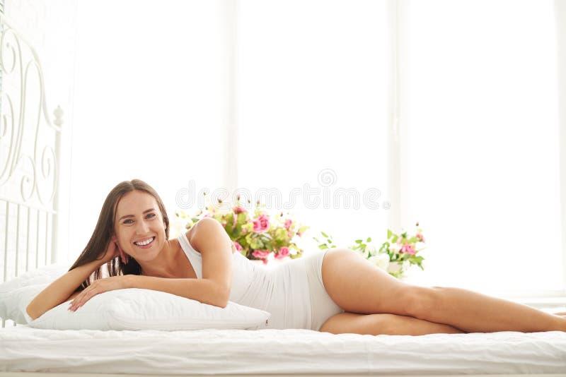 Femme de sourire se réveillant après le sommeil et le mensonge sur le drea de lit images libres de droits