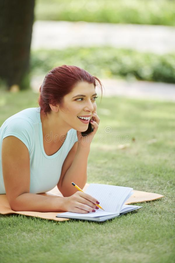 Femme de sourire se reposant sur le campus photo stock