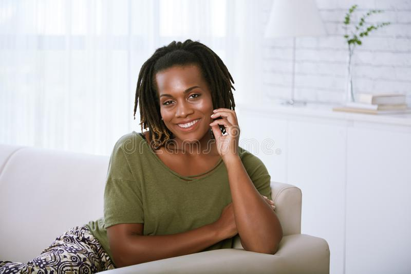 Femme de sourire se reposant sur le sofa images libres de droits