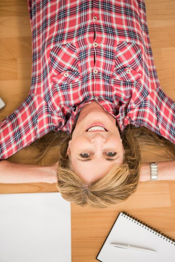 Femme de sourire se trouvant sur le plancher entouré par des articles de bureau images stock