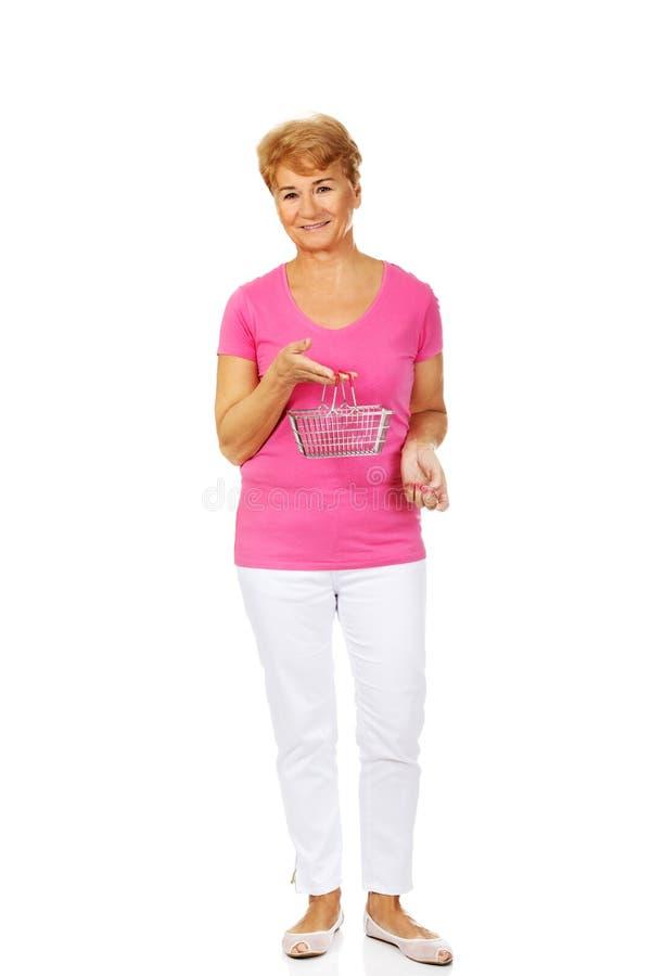 Femme de sourire supérieure tenant le mini panier à provisions image libre de droits