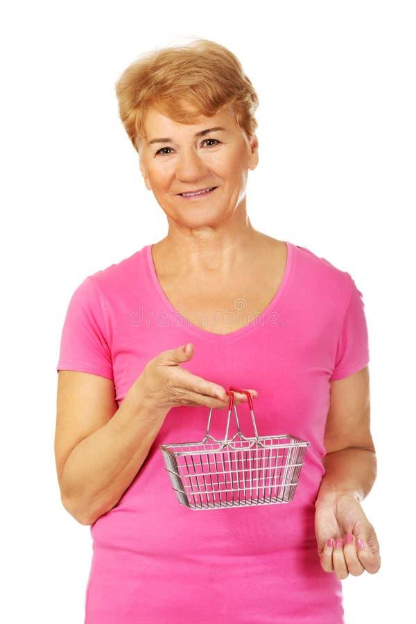 Femme de sourire supérieure tenant le mini panier à provisions images libres de droits