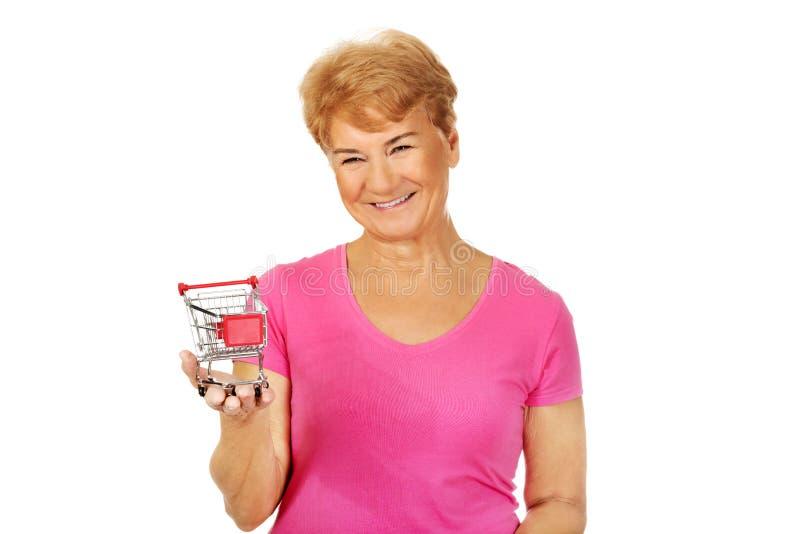 Femme de sourire supérieure tenant le petit chariot photographie stock libre de droits