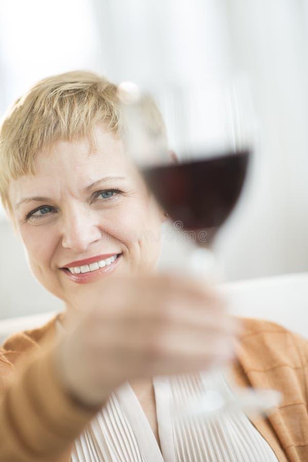 Femme de sourire supportant le verre à vin rouge images stock