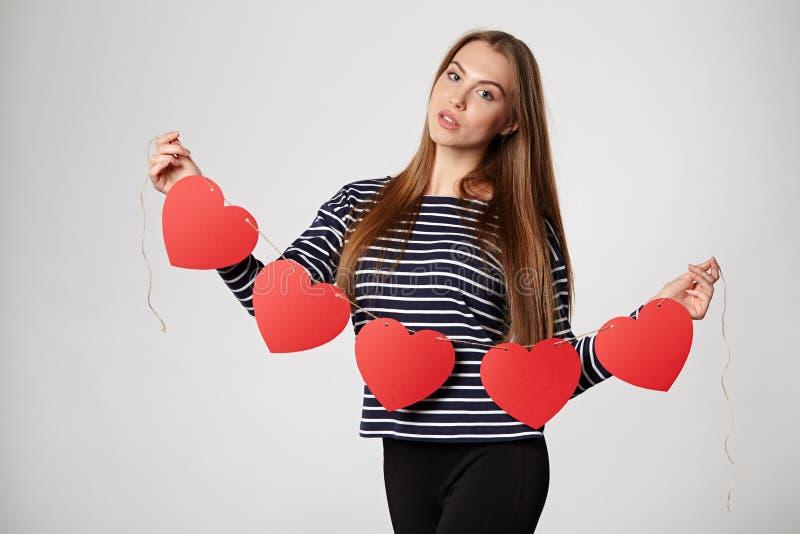 Femme de sourire tenant la guirlande de cinq coeurs de papier rouges images stock