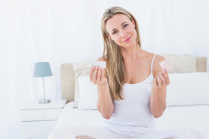 Femme de sourire tenant la pilule et le préservatif photo libre de droits