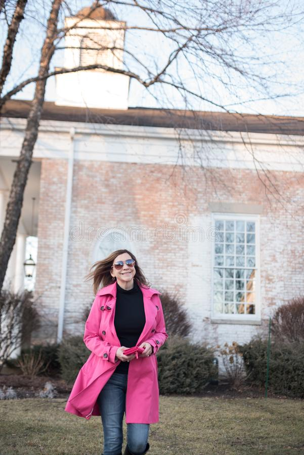 Femme de sourire tenant le portefeuille marchant hors de la banque - f surexposé images libres de droits