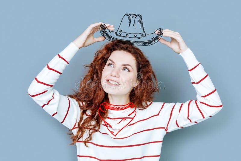 Femme de sourire tenant un chapeau de cowboy tout en étant à la partie de costume image libre de droits