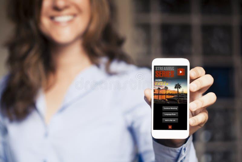 Femme de sourire tenant un téléphone portable dans la main avec couler la vidéo APP dans l'écran photographie stock