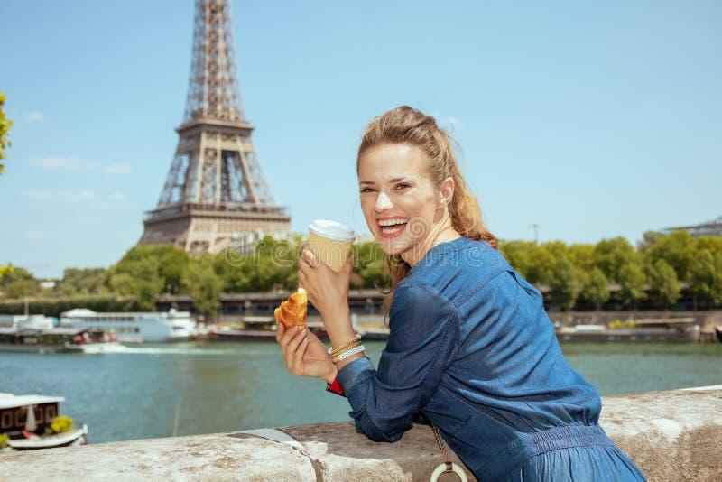 Femme de sourire de voyageur avec la tasse du café et du croissant photographie stock libre de droits