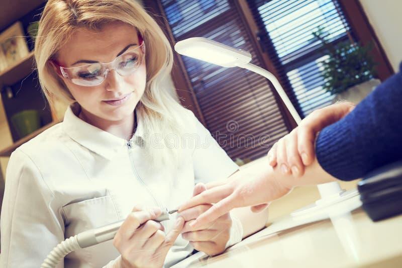 Femme de spécialiste en manucure faisant le soin d'ongle de doigt de courrier photos libres de droits