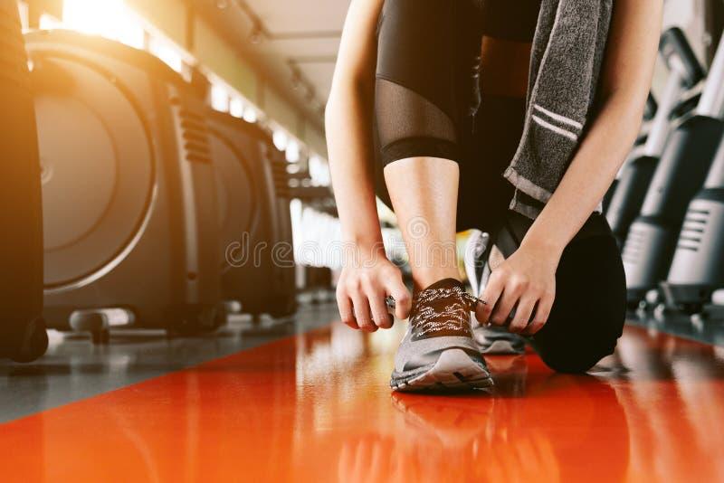 Femme de sport attachant la corde d'espadrilles Centre de sport et concept de gymnase de forme physique Th?me sain et de corps d' images stock