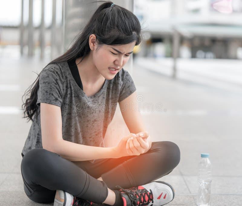 Femme de sport ayant une blessure sur sa main de poignet images stock