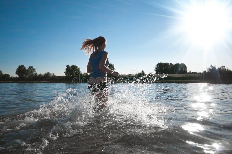 Femme de sport exécutant dans l'eau photographie stock