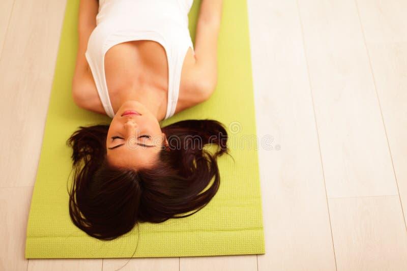 Femme de sport sur le tapis de yoga images libres de droits