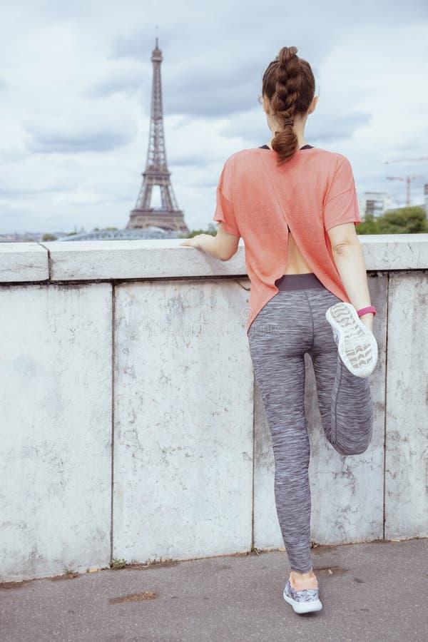 Femme de sports devant l'étirage de Tour Eiffel images libres de droits