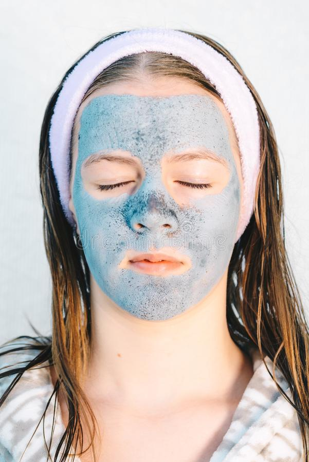 Femme de station thermale appliquant le masque facial d'argile Traitements de beaut? photo stock