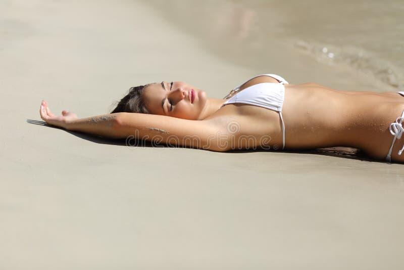 Femme de Sunbather montrant l'aisselle d'épilation de laser sur la plage image libre de droits