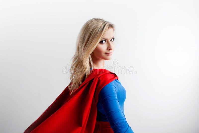 Femme de super héros examinant la distance la droite Jeune et belle blonde dans l'image du superheroine, arrière photos libres de droits