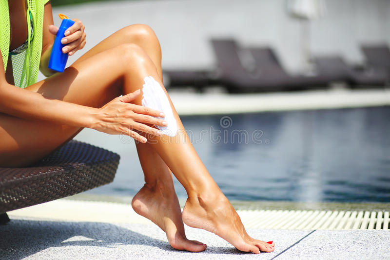 Femme de Tan appliquant la lotion de protection du soleil images stock