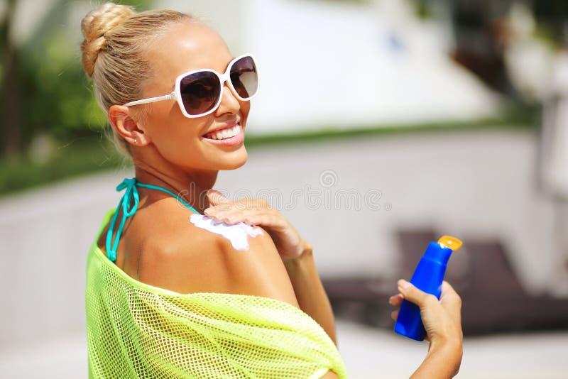 Femme de Tan appliquant la lotion de protection du soleil images libres de droits