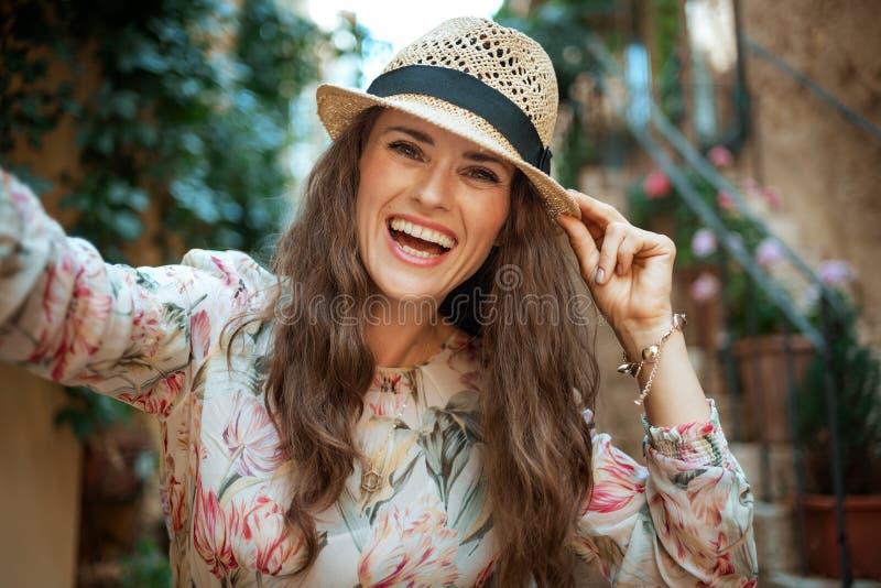 Femme de touristes élégante de sourire dans la vieille ville de l'Europe prenant le selfie image stock