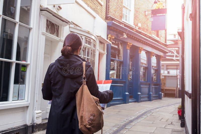 Femme de touristes asiatique regardant la carte sur la rue de la ville image libre de droits