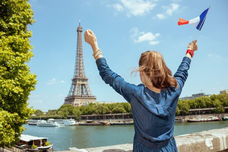 Femme de touristes avec la réjouissance de drapeau de la France à Paris, France image libre de droits