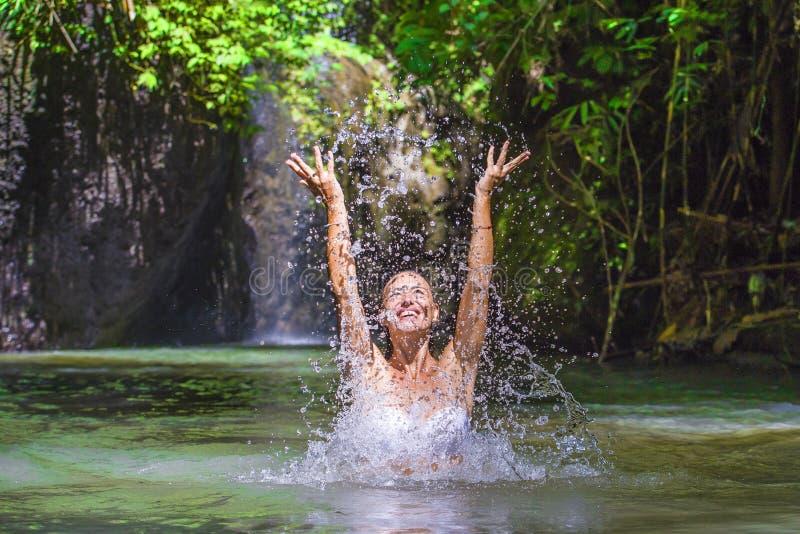 Femme de touristes blanche heureuse attirante appréciant jouer avec l'eau et l'éclaboussure au voyage exotique tropical Co de vac image stock