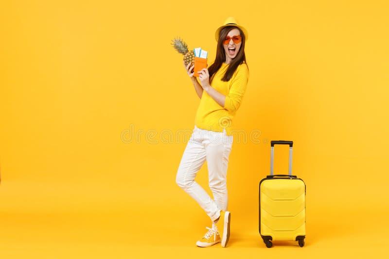 Femme de touristes criarde de voyageur dans le passeport de prise de chapeau, billets, fruit frais d'ananas d'isolement sur jaune images stock