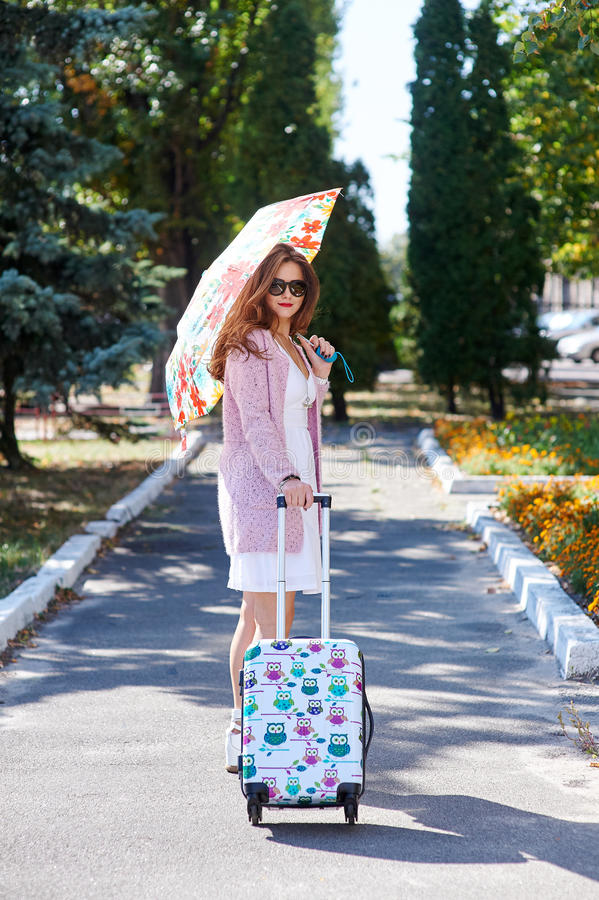 Femme de touristes heureuse dans les lunettes de soleil et le parapluie avec la valise marchant en parc photos libres de droits