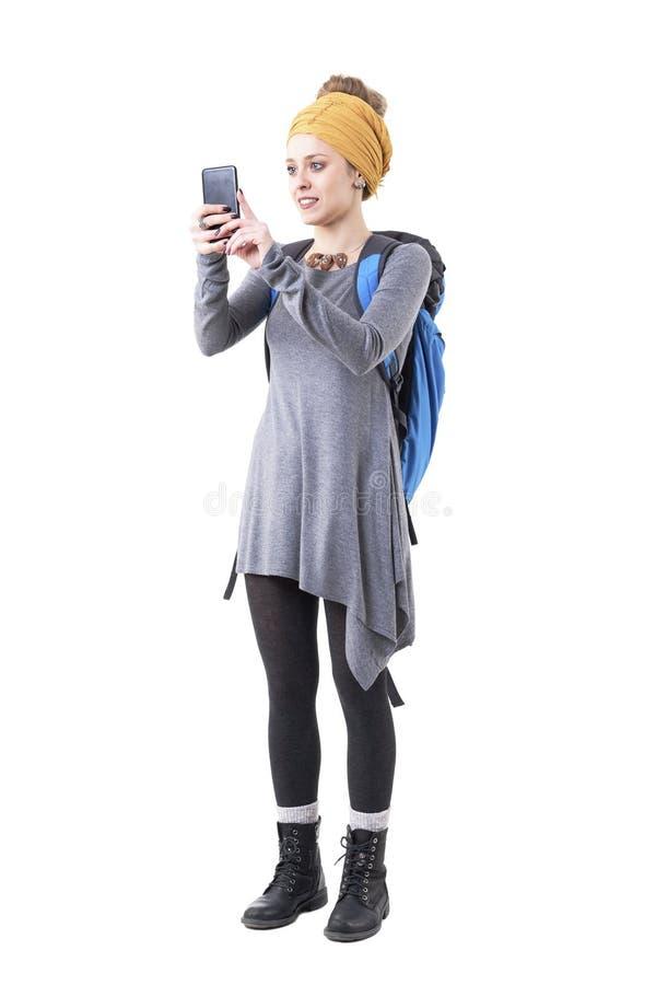 Femme de touristes de jeune hippie heureux avec le sac à dos visitant le pays et prenant la photo avec le téléphone intelligent image stock