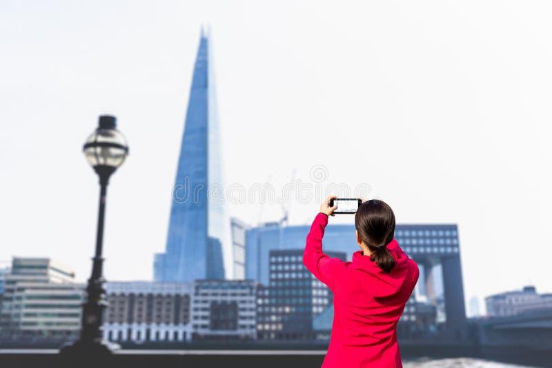 Femme de touristes prenant la photo du bâtiment et de la Tamise avec le téléphone portable photo libre de droits