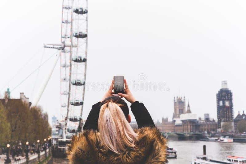 Femme de touristes prenant la photo de London Eye avec le t?l?phone portable par la Tamise photo stock