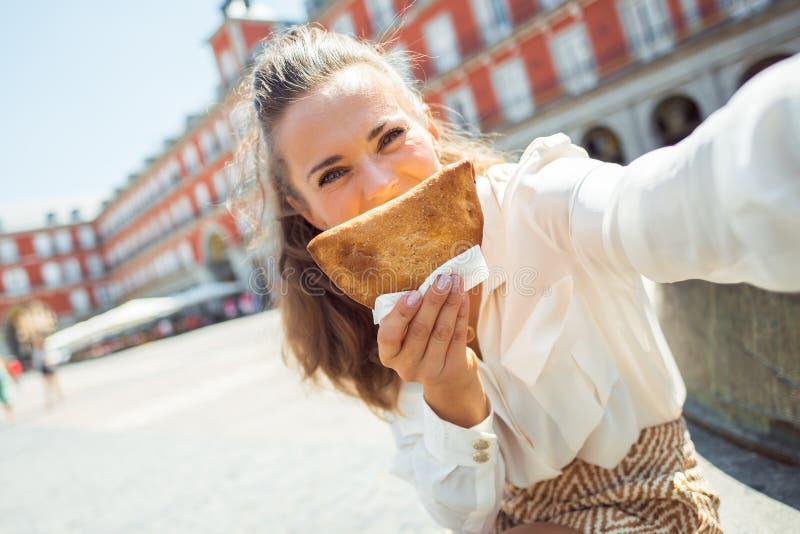 Femme de touristes prenant le selfie tout en faisant le sourire avec Empanada photographie stock