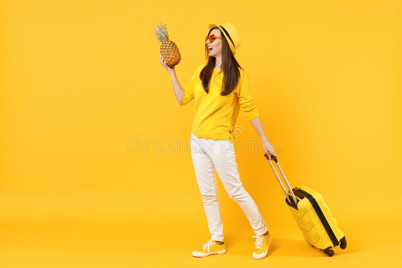 Femme de touristes riante de voyageur dans des vêtements d'été, fruit mûr frais d'ananas de prise de chapeau d'isolement sur jaun photo stock