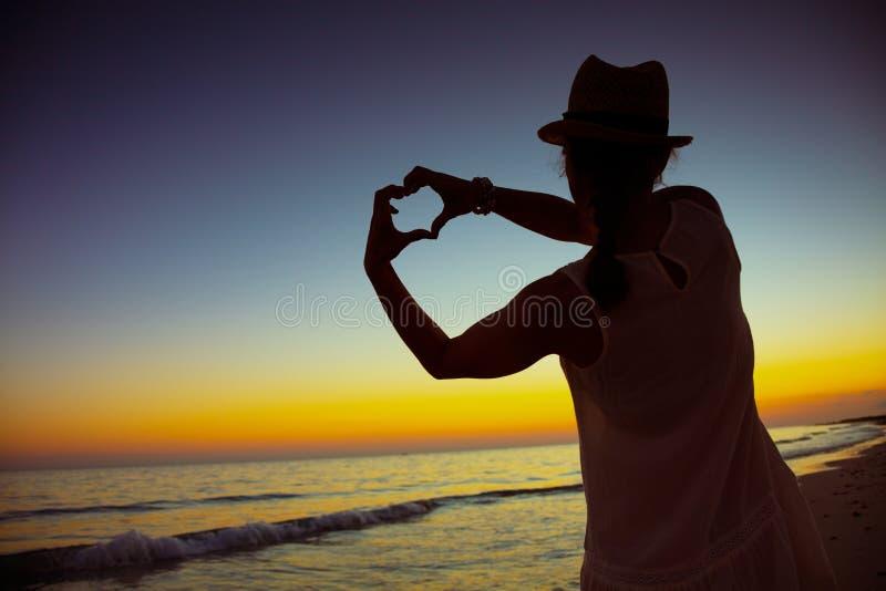 Femme de touristes soloe active montrant les mains en forme de coeur photographie stock libre de droits
