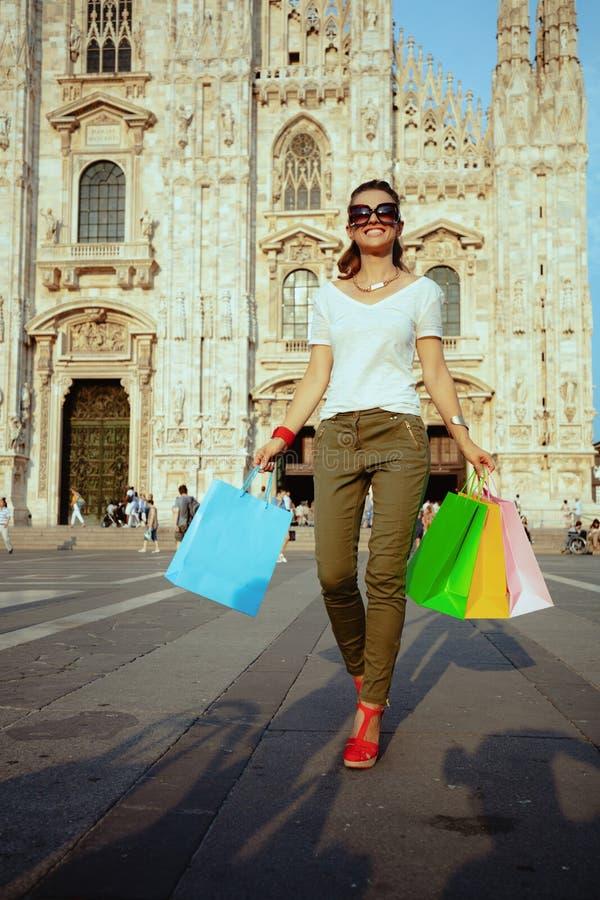 Femme de touristes soloe de sourire marchant avec les sacs à provisions colorés photos libres de droits