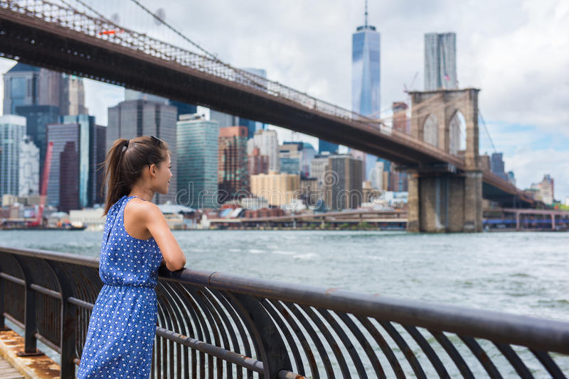 Femme de touristes urbaine de New York City regardant le pont de Brooklyn et l'horizon photos stock