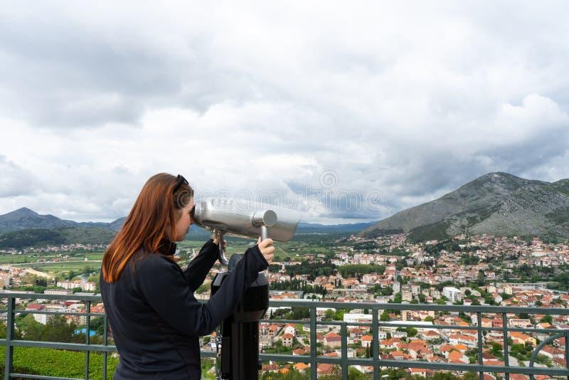 Femme de touristes de voyage des vacances de l'Europe La fille de hippie ? l'aide du t?lescope regarde le panorama de la ville D? photos stock