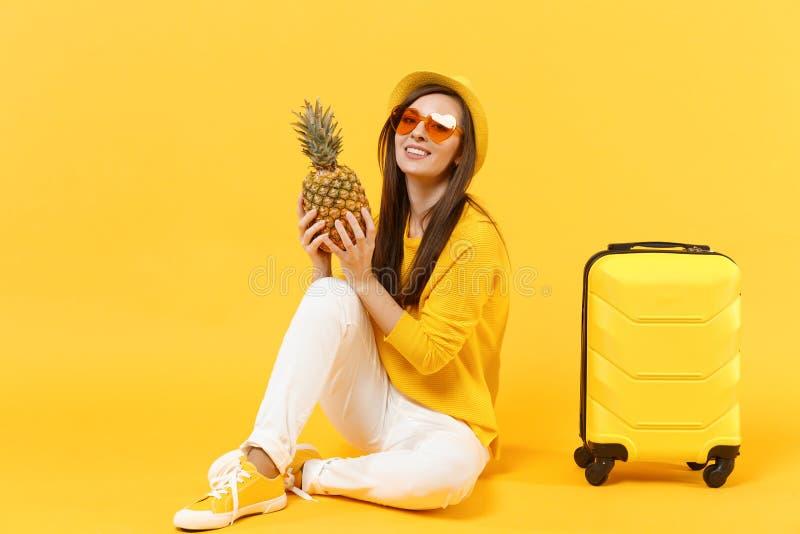 Femme de touristes de voyageur dans des vêtements sport d'été, fruit mûr frais d'ananas de prise de chapeau d'isolement sur jaune photos stock